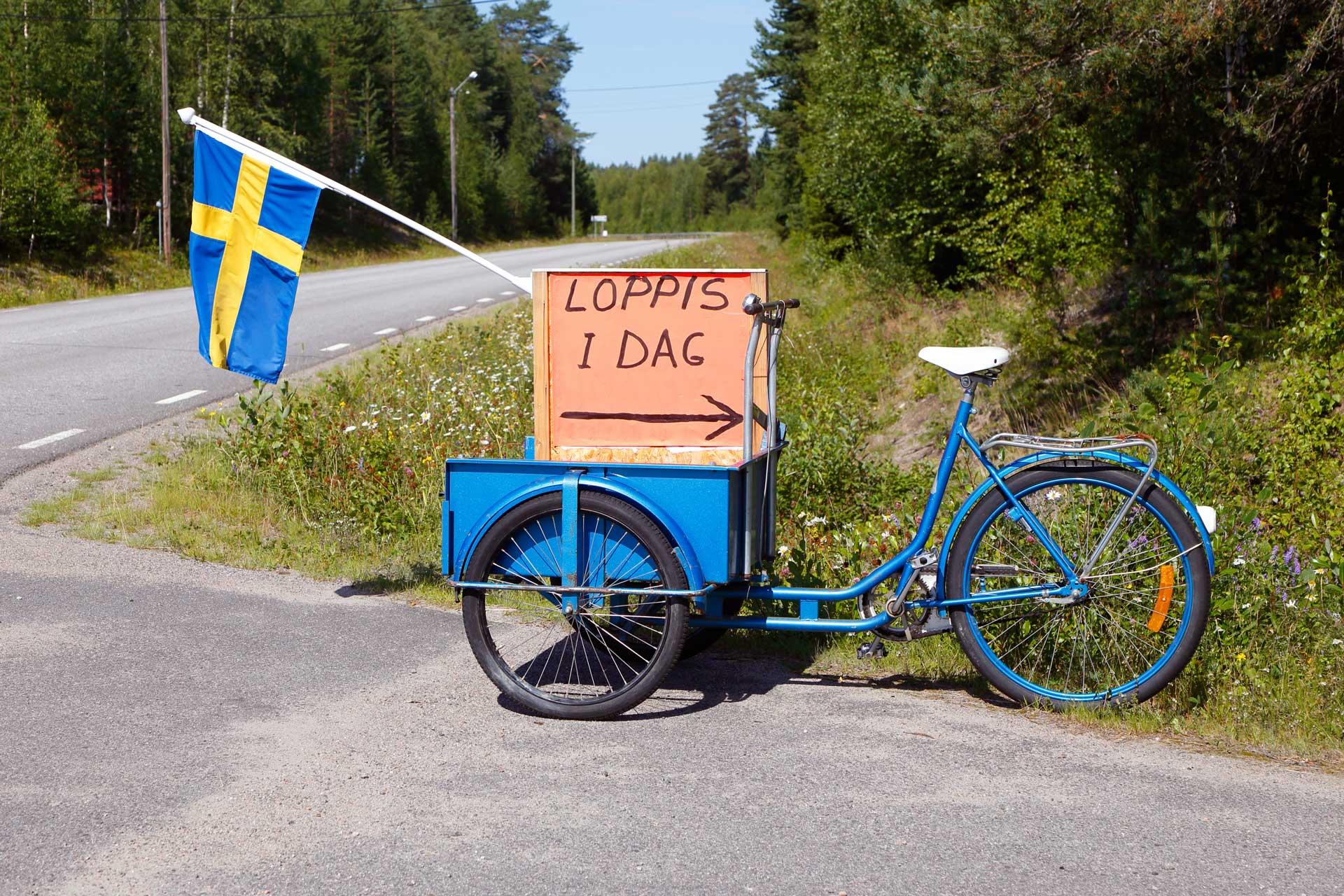 """En blå flakcykel med flagga och skylt """"Loppis idag"""". Fotograf: Mostphotos"""