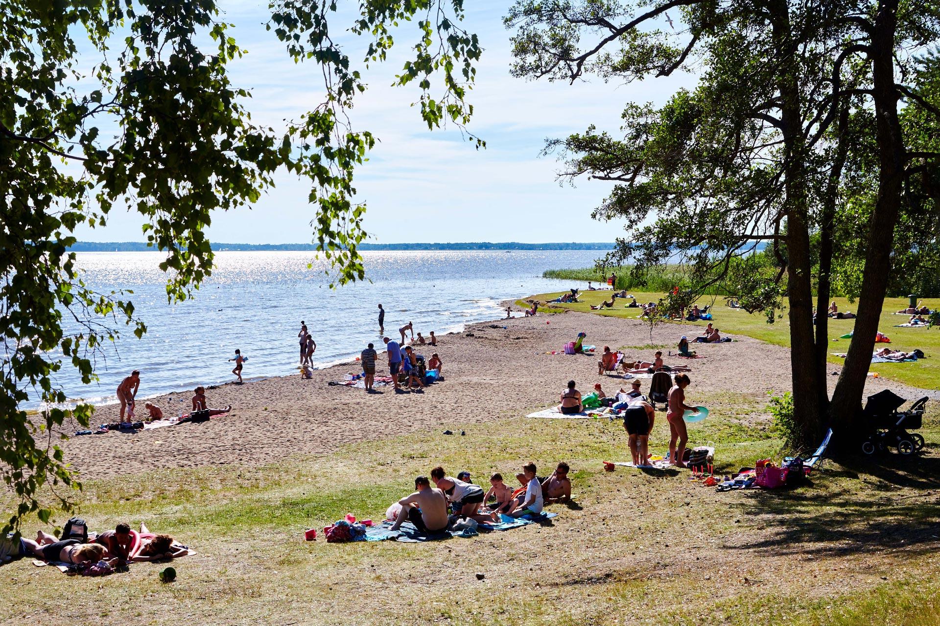 Vy över badstranden på Björnö med besökare som badar och solar. Fotograf: Pia Nordlander