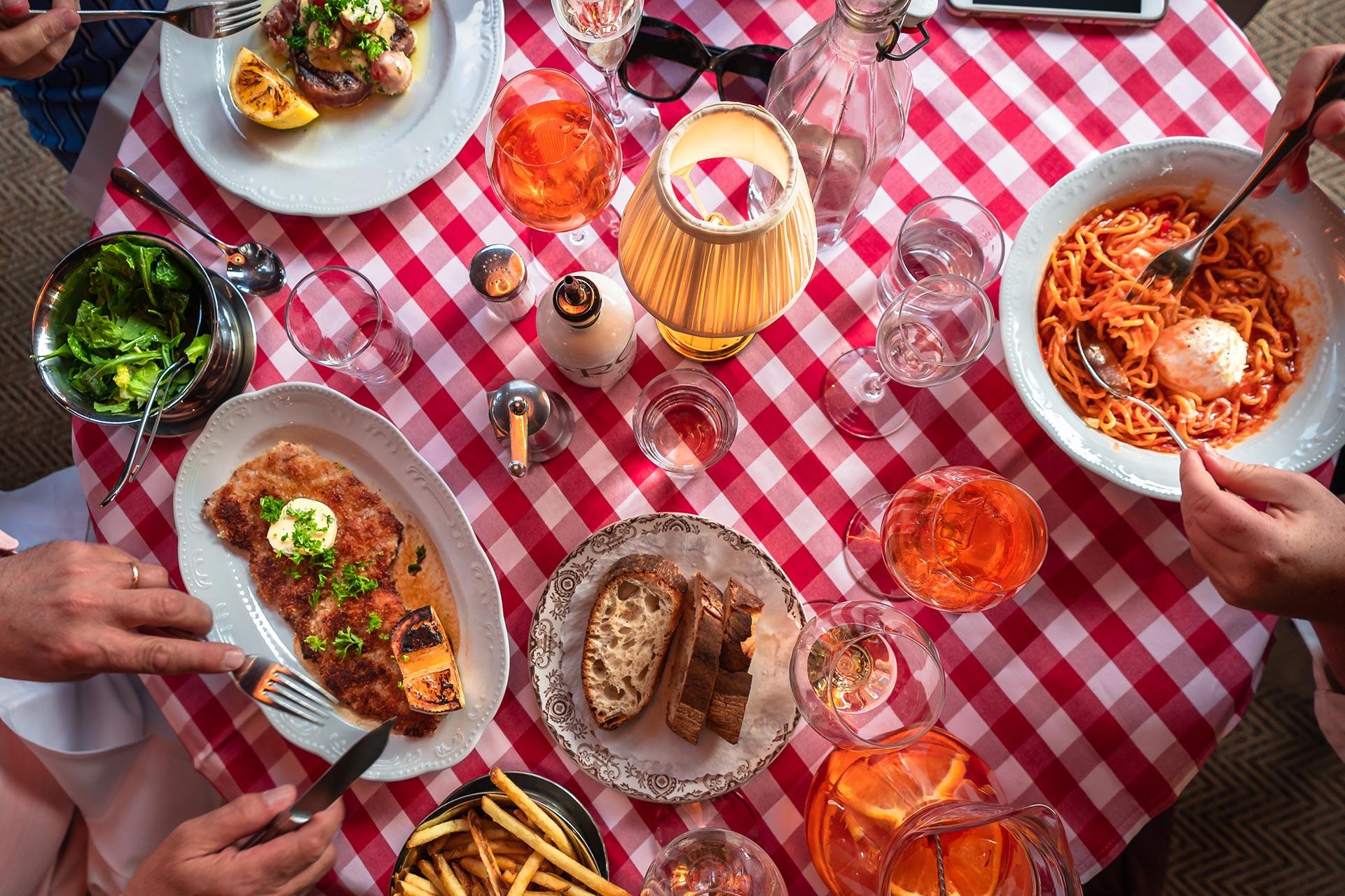 Tallrikar med olika maträtter på en restaurang med röd/vit rutig bordsduk. Fotograf: Findie