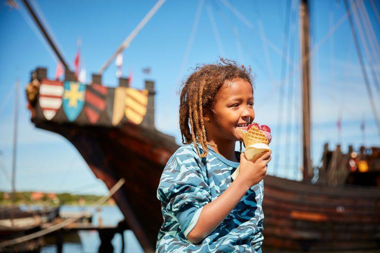 Ett barn äter en glass på Frösåkers Brygga i Västerås med ett stort vikingaskepp i bakgrunden. Foto: BildN
