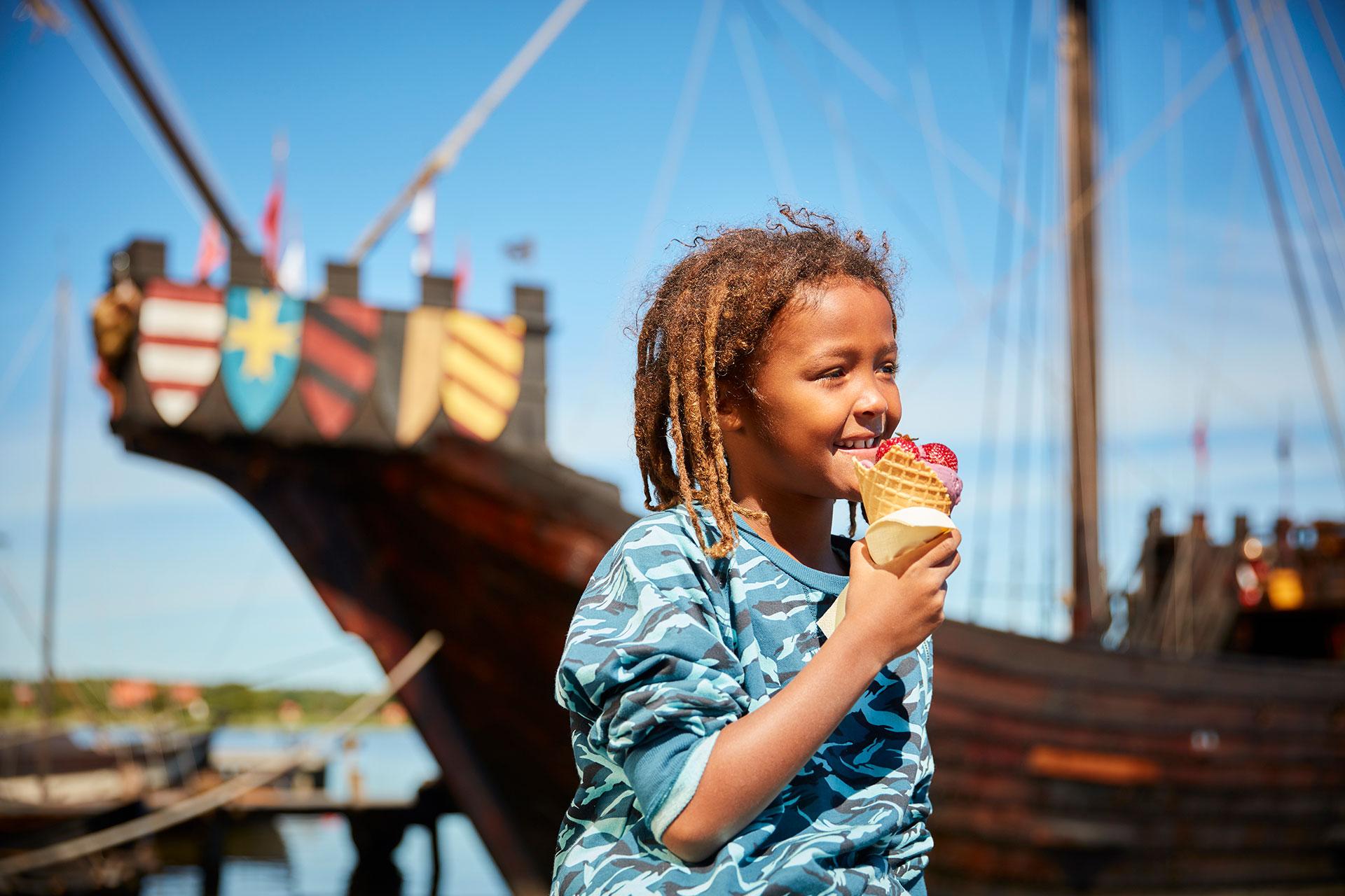 Ett barn äter en glass på Frösåkers Brygga med ett stort vikingaskepp i bakgrunden. Fotograf: BildeN