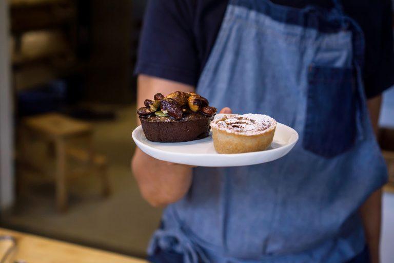 Konditor på Kopparlundens bageri serverar bakelser. Fotograf: Findie