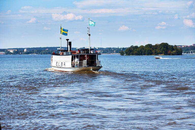 Elbafärgan åker runt på Mälaren med svenska flaggan och Rederi Mälardalens flagga som svajar. Fotograf: Pia Nordlander