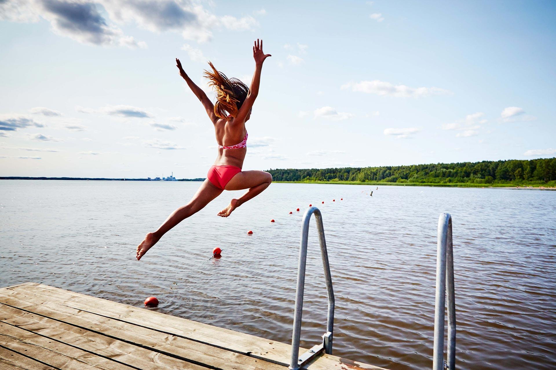 Ett barn hoppar i mälaren från en brygga en solig sommardag. Fotograf: Pia Nordlander