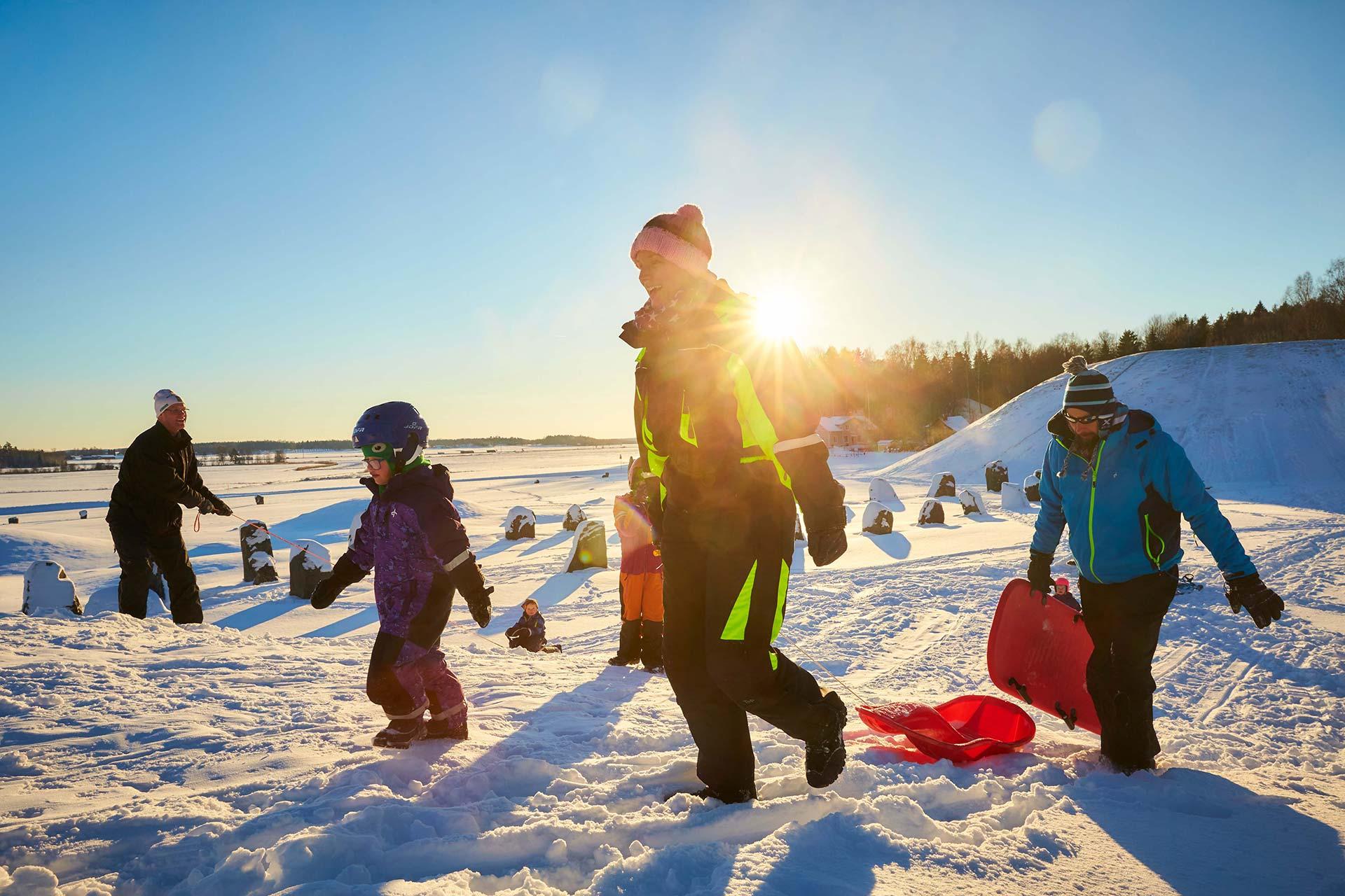 Pulkaåkning i vinterlandskap med solnedgång, på Anundshög i Västerås. Foto: BildN