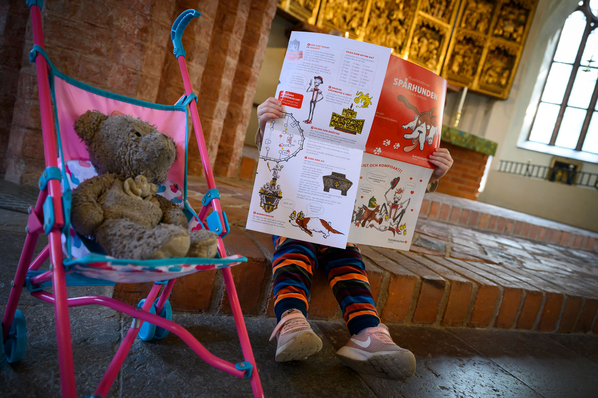 Ett litet barn sitter i Domkyrkan och tittar i en broschyr om Spårhunden. Fotograf: Magnus Aronsson