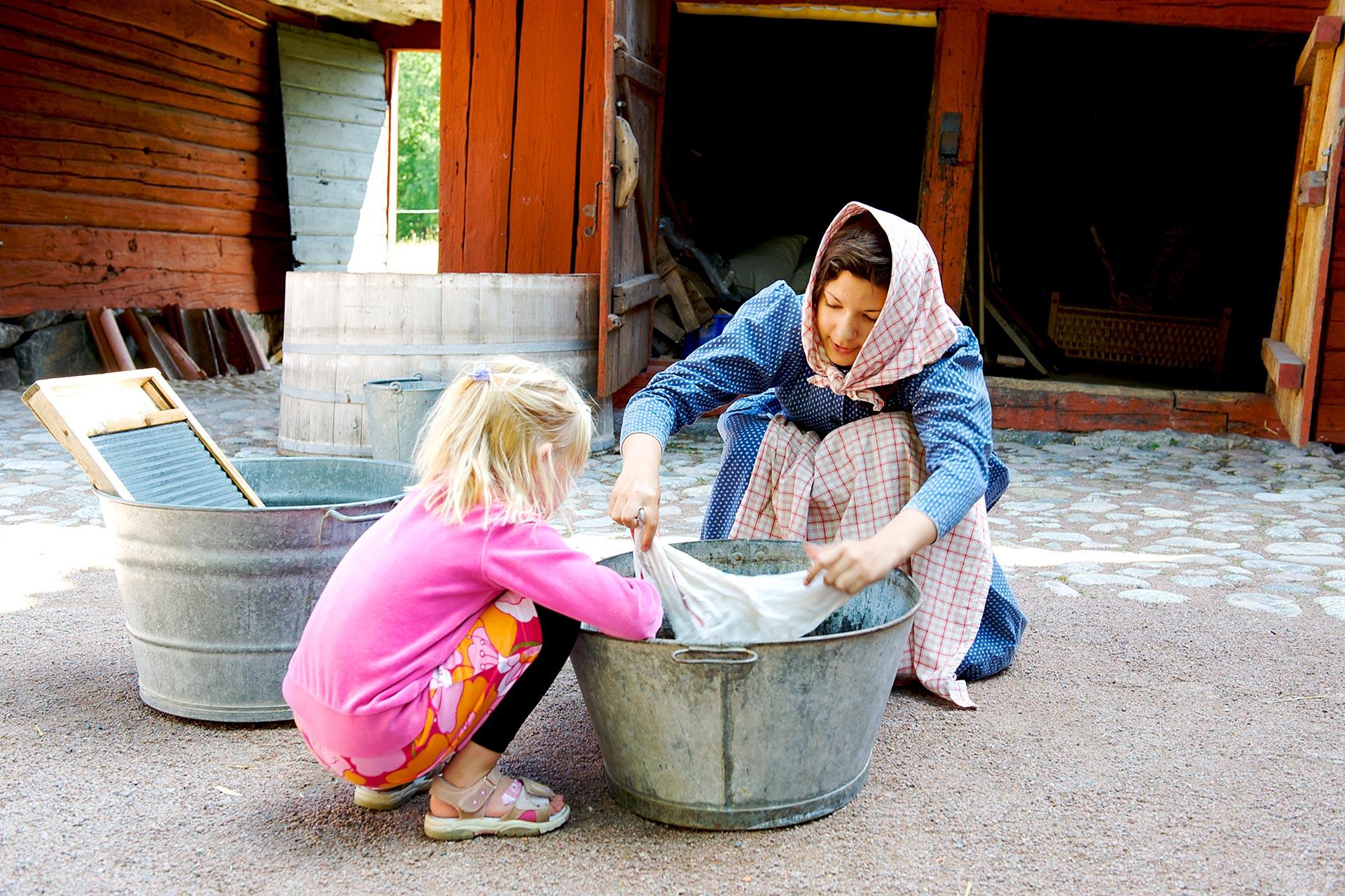 En kvinna från Vallby Fridluftsmuseum i Västerås utklädd till piga tvättar tvätt i tvättbalja med ett barn som är på besök. Fotograf: Leon Grimaldi