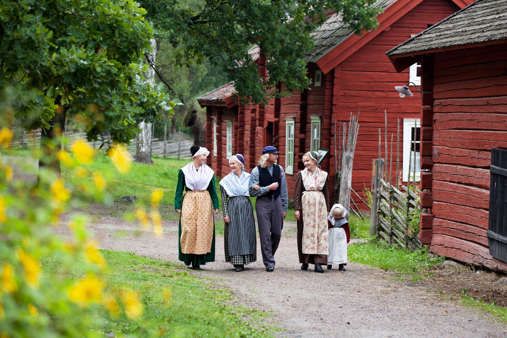 Barn, vuxna och äldre i tidsenliga kläder på Vallby Friluftsmuseum i Västerås. Fotograf: Laila Duran