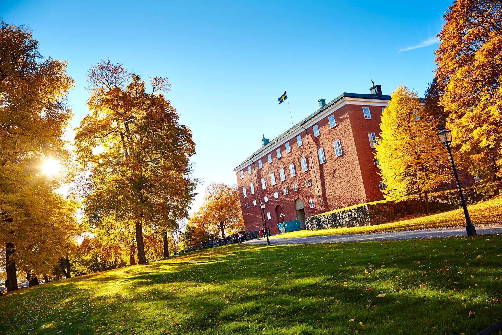 Västerås slott i motljus. Löv i guldfärger pryder träden och en grupp besökare lyssnar på guide. Fotograf: Pia Nordlander