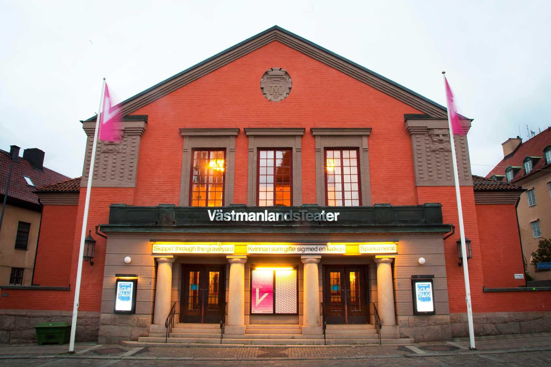 Västmanlands Teater i orange teagel med rosa flaggor som vajar. Fotograf: Kim Norman