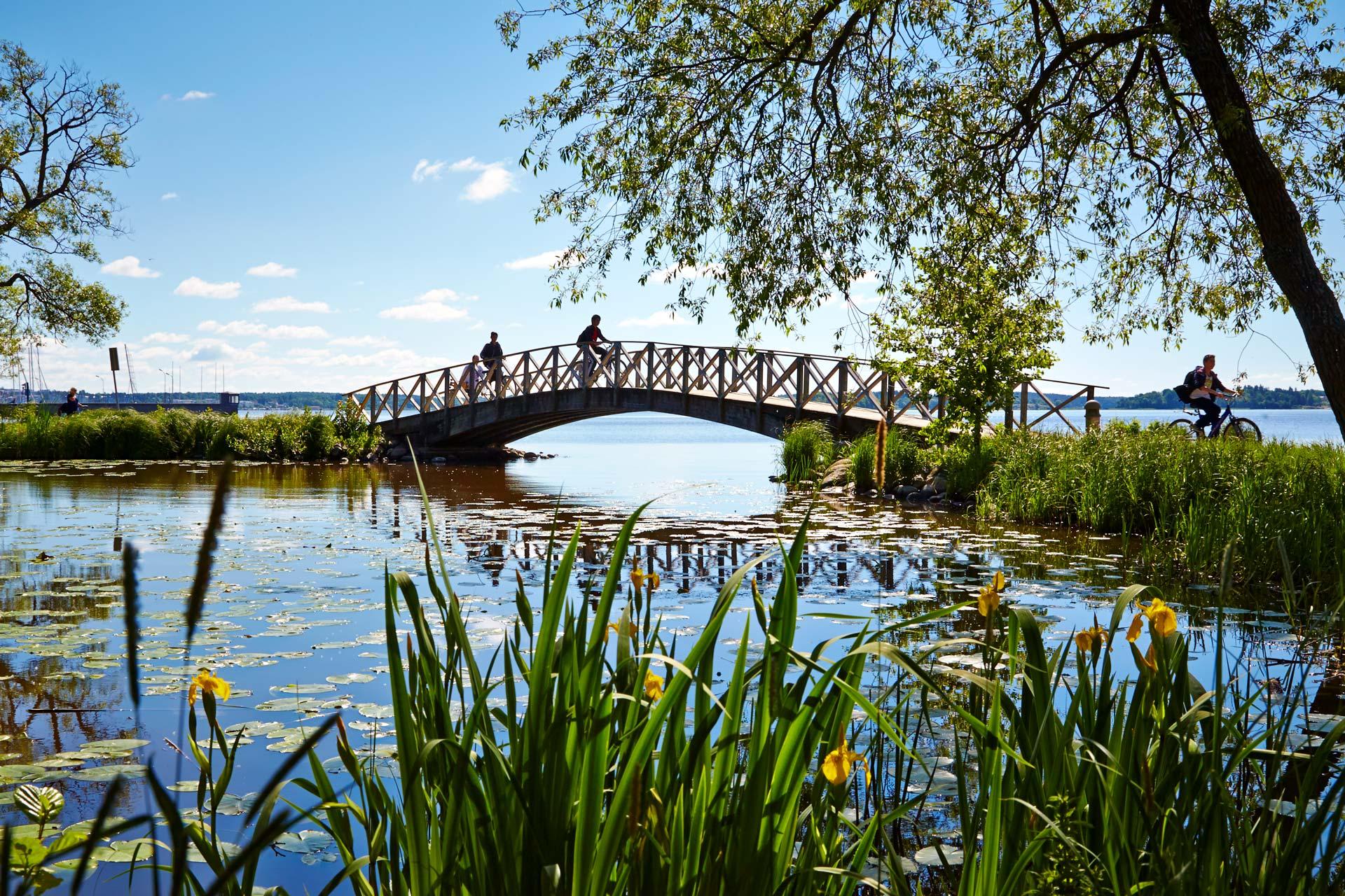 En solig sommardag med cyklister som cyklar över bro vid Mälaren. Fotograf: Hans Nordlander