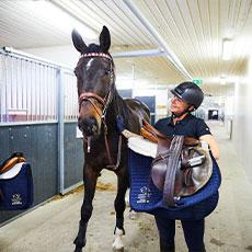 En tjej som står med en häst inne på Rocklunda Ridskola. Foto: Pressbild