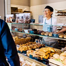 Massor med bakverk och smörgåsar där en glad kvinna på bageriet betjänar en kund.