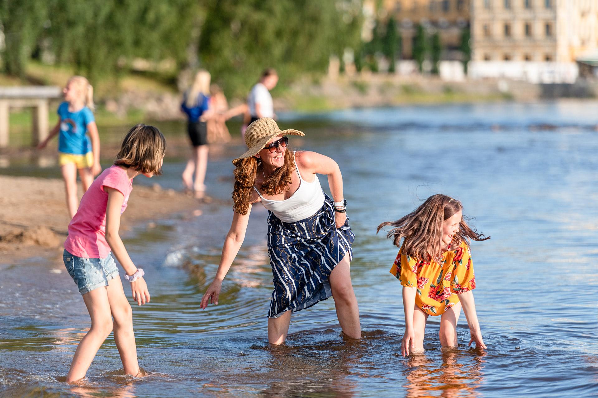 En familj svalkar sig i vattnet.