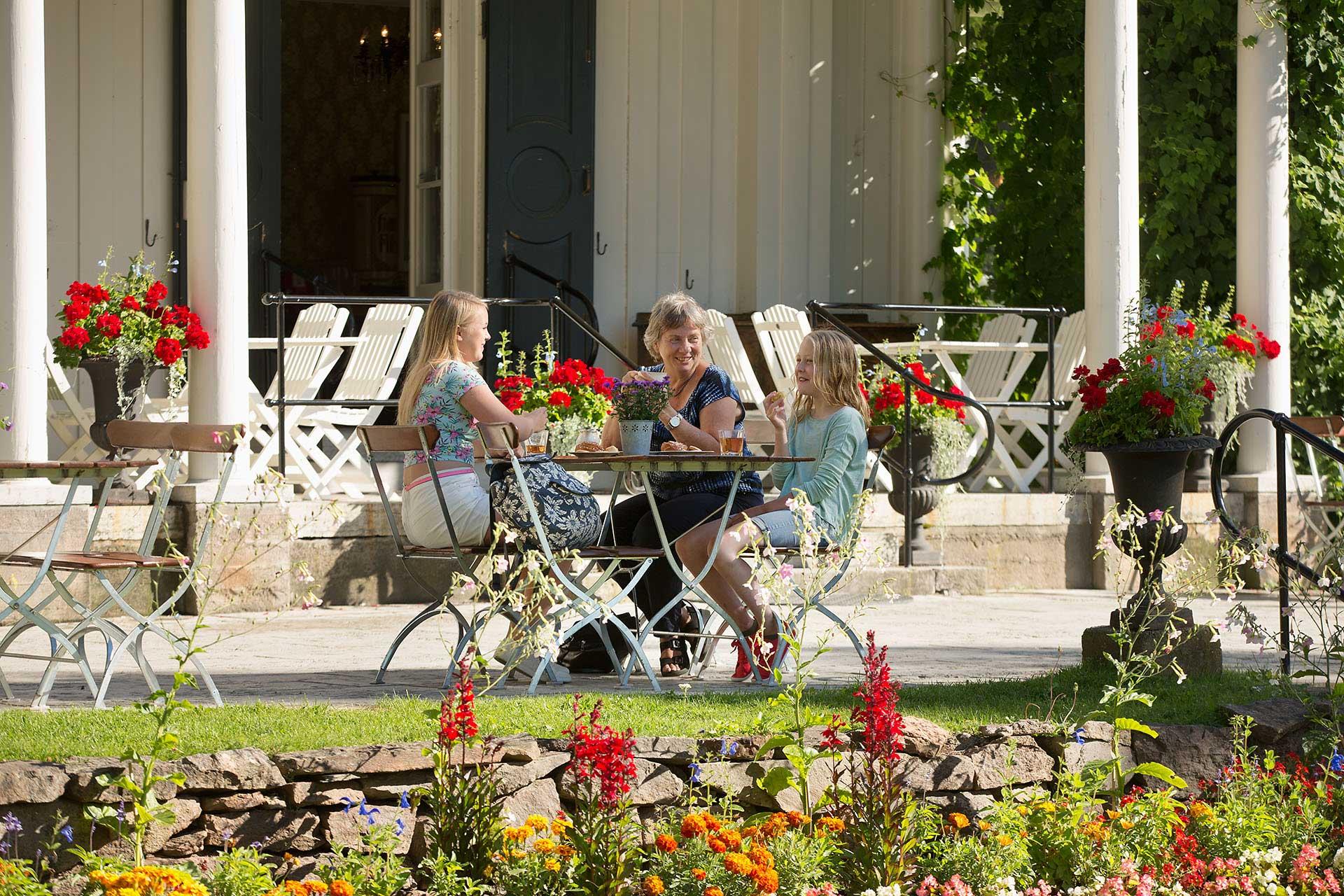 En familj sitter på Alster Herrgård och fikar.