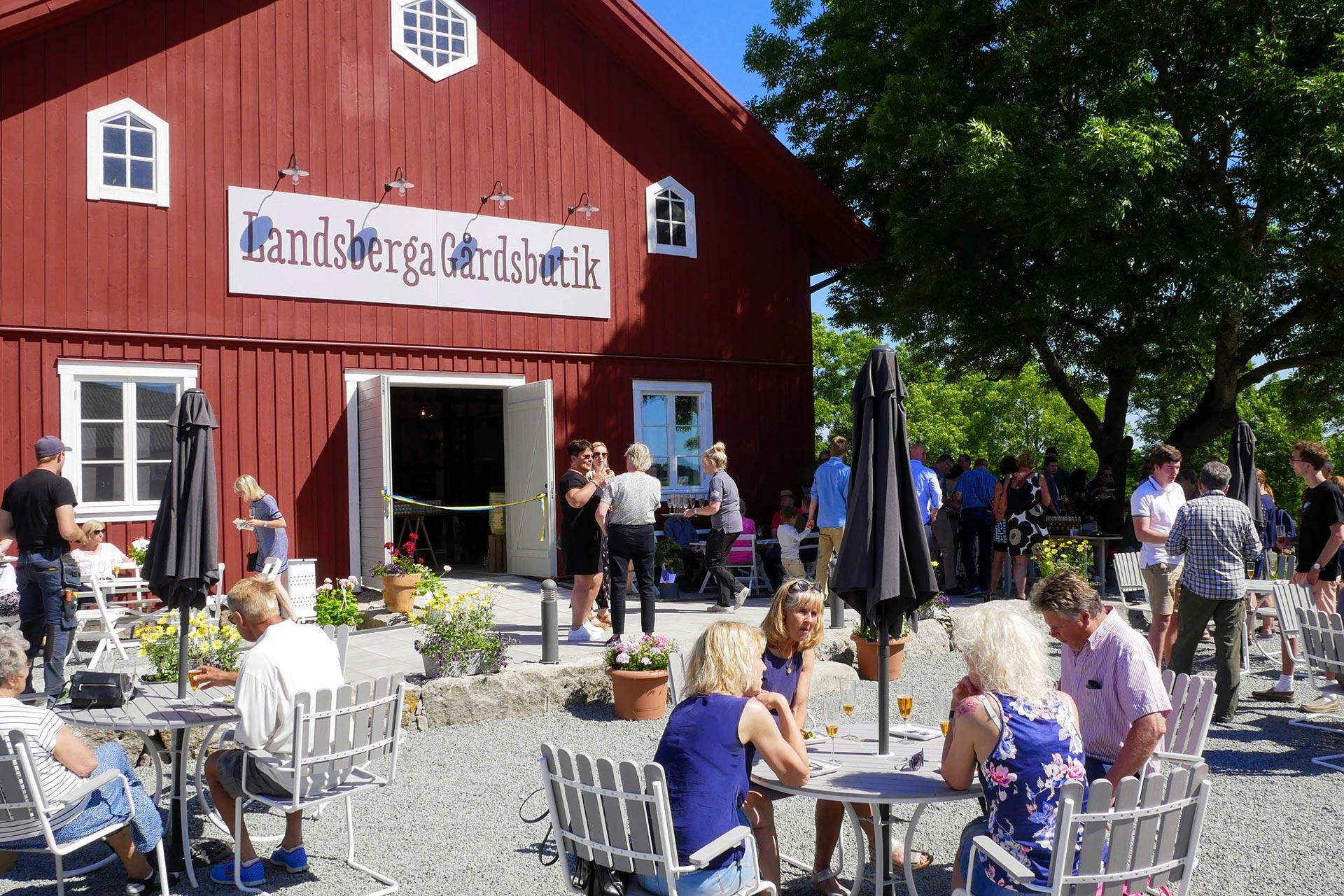 Folk sitter och fikar vid bord på Ladsberga gårdsbutik. Fotograf: Mats Thorburn