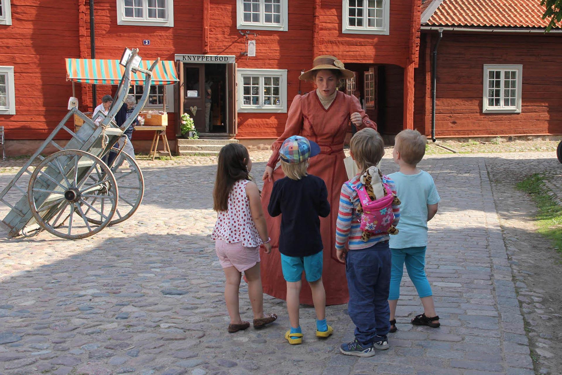 En kvinna hade kläder från förr och barn i ring framför henne.