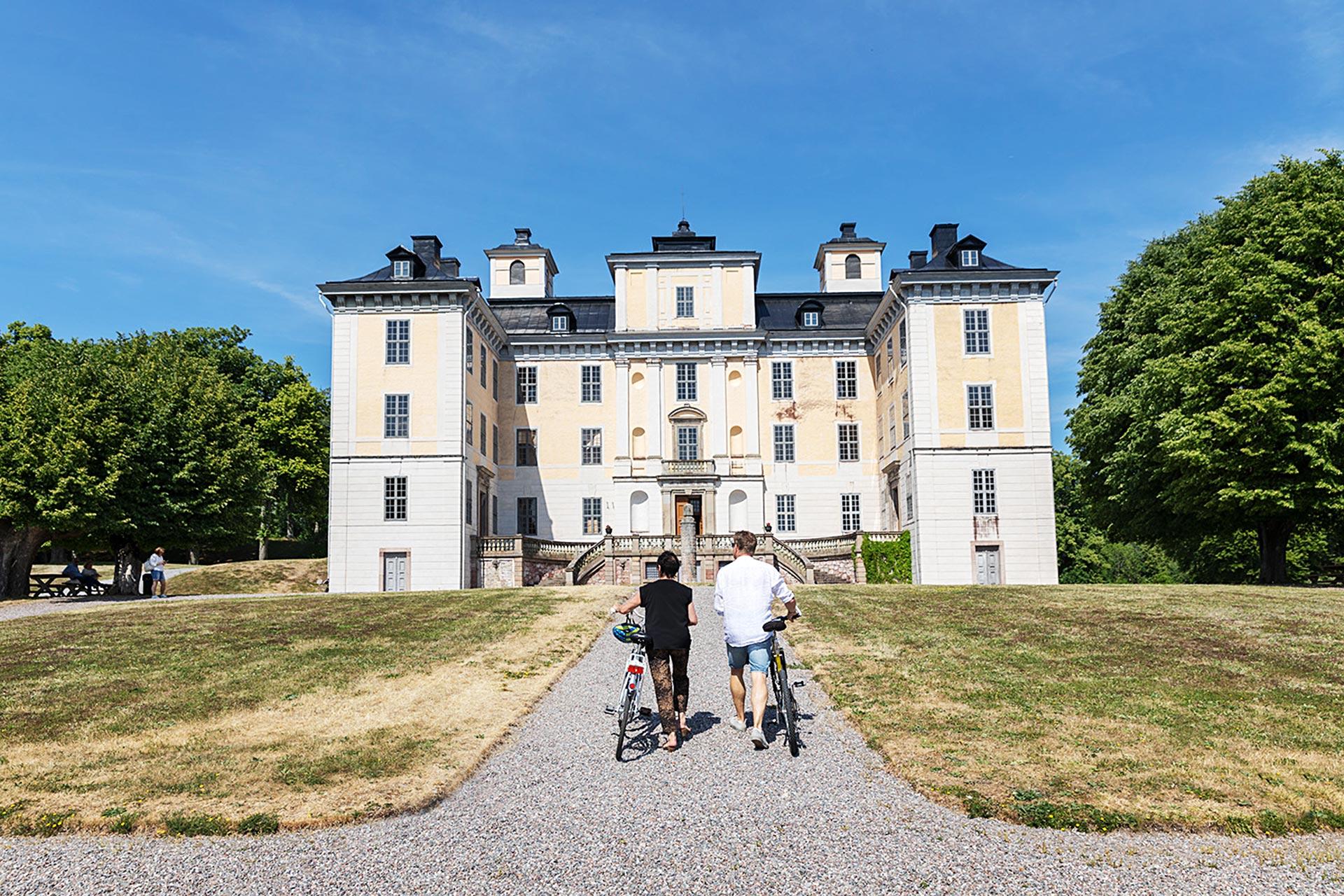 Två personer med cyklar går mot Mälsåkers Slott. Foto: Ulf Huett
