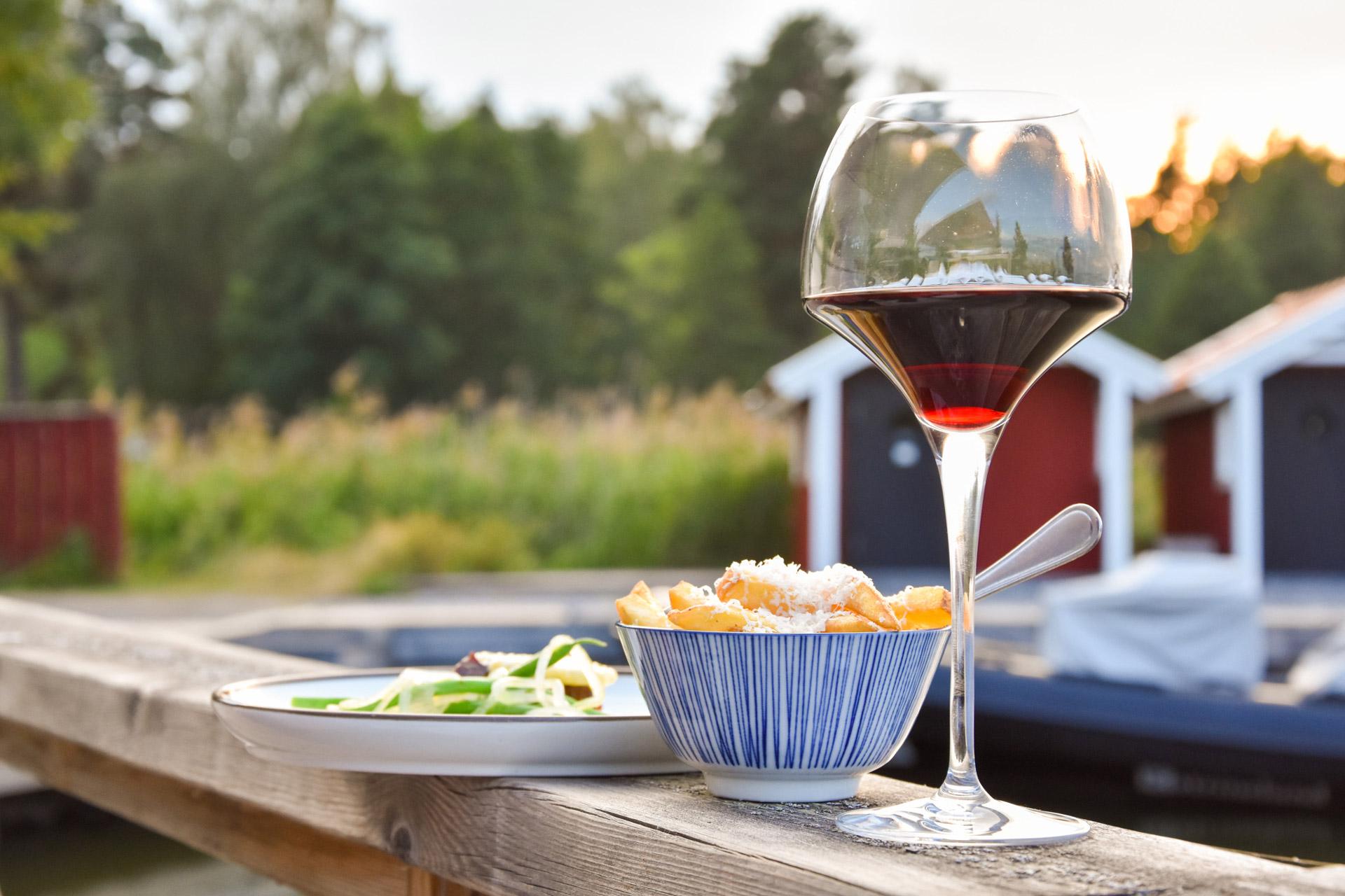 Ett vinglas och en bit mat står på ett räcke vid Katrinelund i Örebro