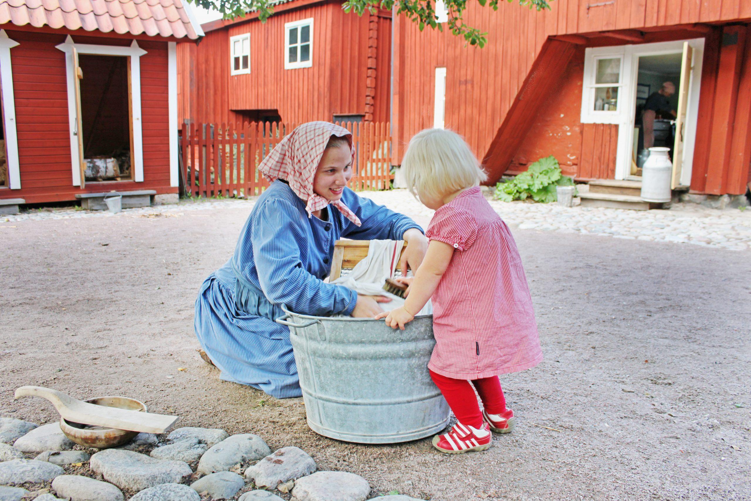 Barn hjälper till att tvätta på klassiskt vis på Vallby friluftsmuseum i Västerås. Foto: Pressbild