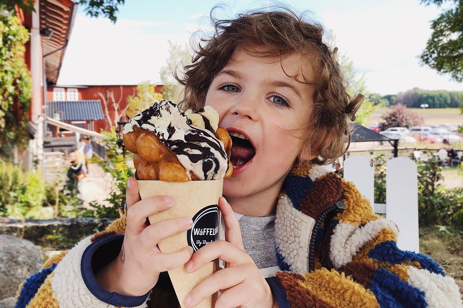 Ett barn äter en stor våffla på Wåffelbaren i Västerås. Fotograf: Matilda Hildingsson