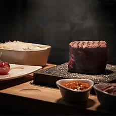 En köttbit på en glödhet lavasten och tillbehör hos Black Stone. Foto: Pressbild