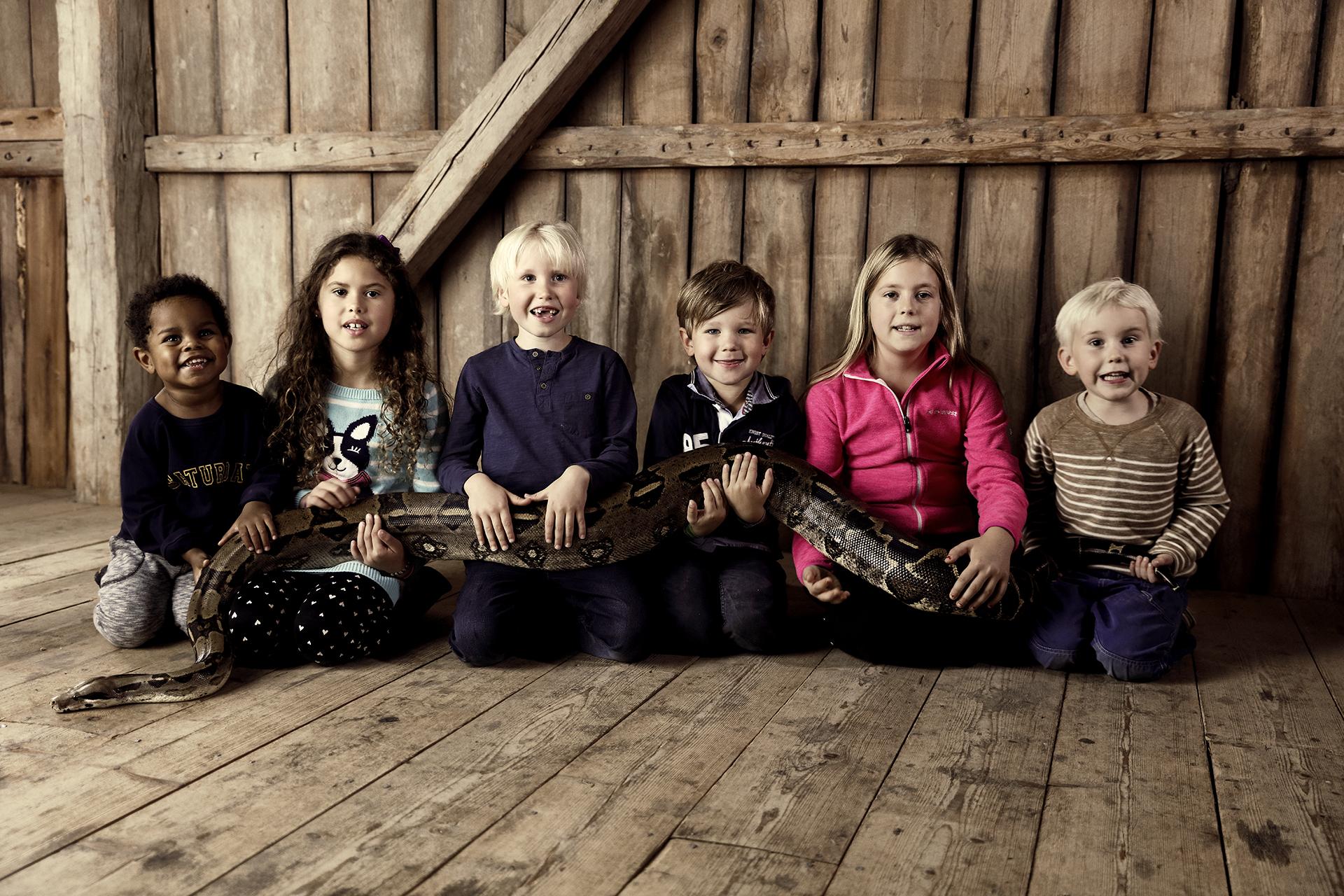 Barn sitter på rad med en lång orm i knät på Kungsbyn i Västerås. Foto: Pressbild