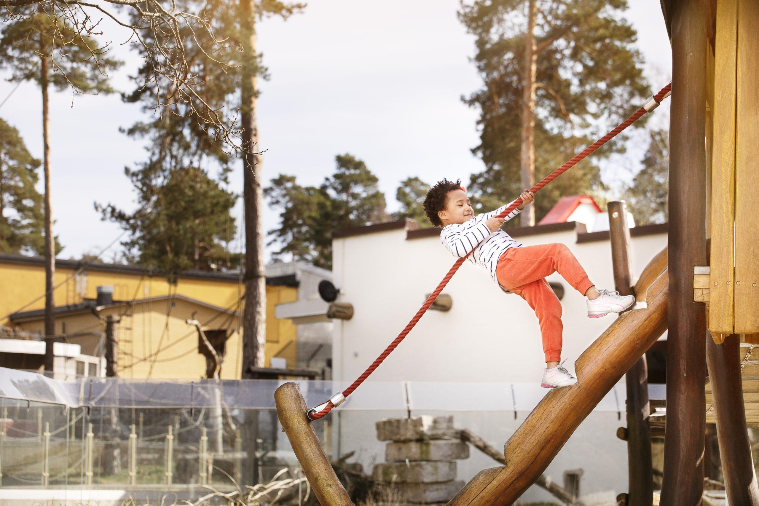 Ett lite kille klättrar upp för ett rep på parken zoo