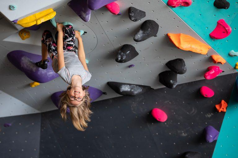 Ett barn hänger upp och ned i en klätterbana hos Klättercentret Västerås. Foto: Pressbild