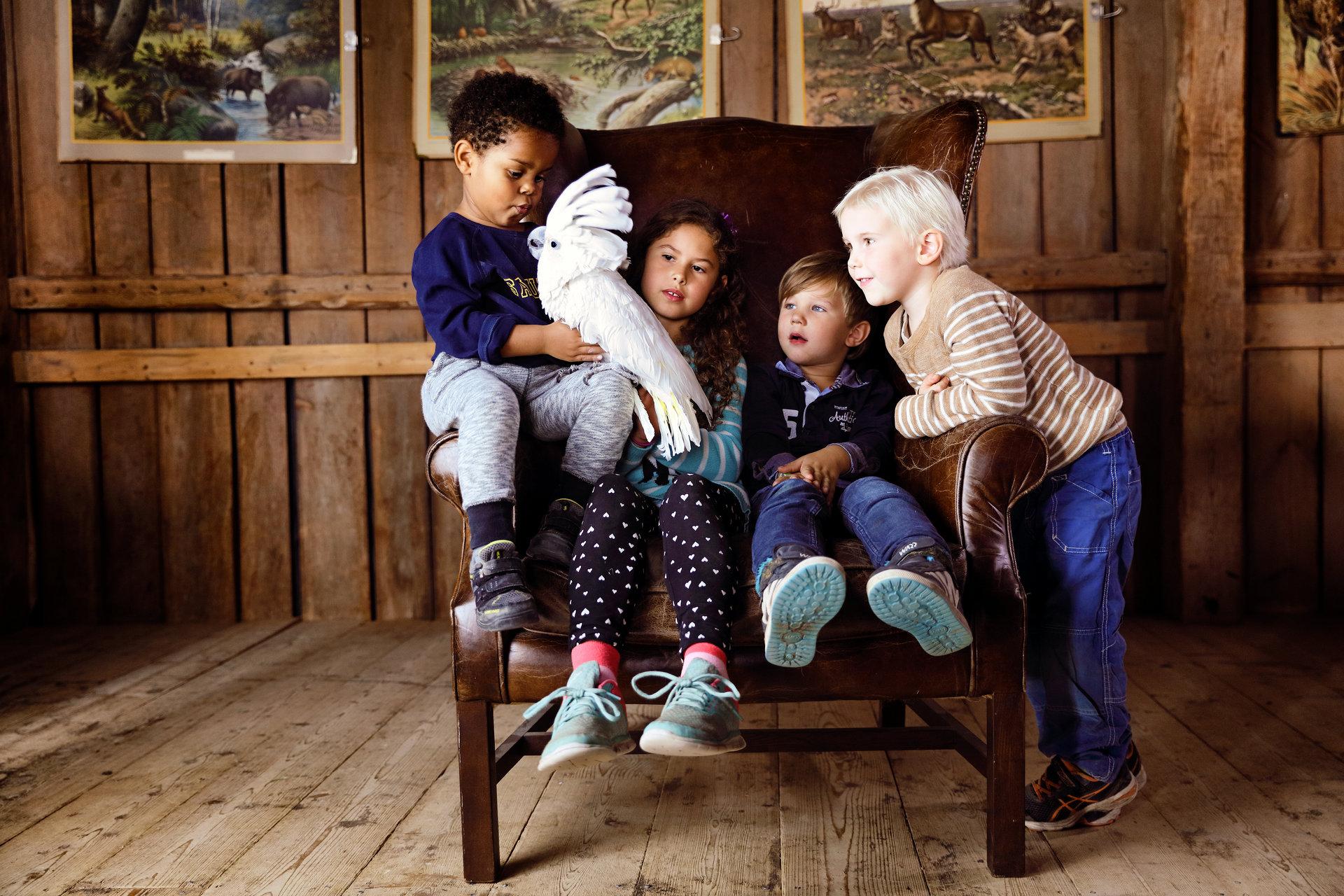 Fyra barn sitter tillsammans i en stol med en papegoja på Kungsbyn. Foto: Pressbild