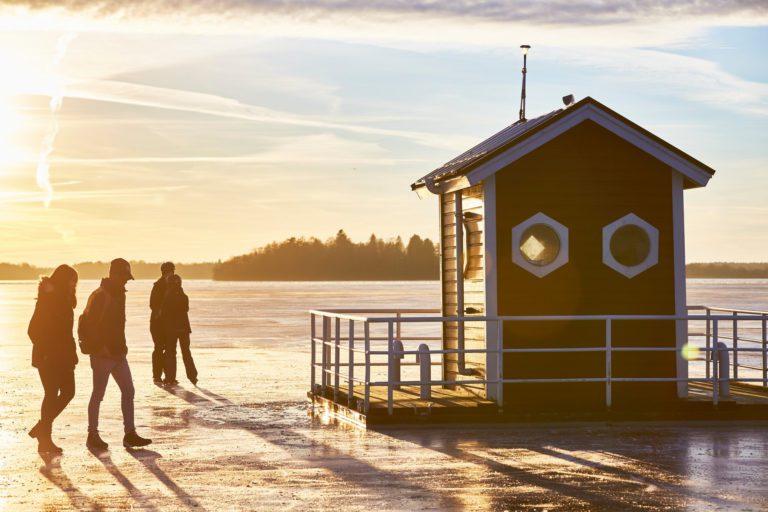 Hotell utter in i vinterskrud där personer vandrar på isen tittar nyfiket på huset. Fotograf: Pia Nordlander