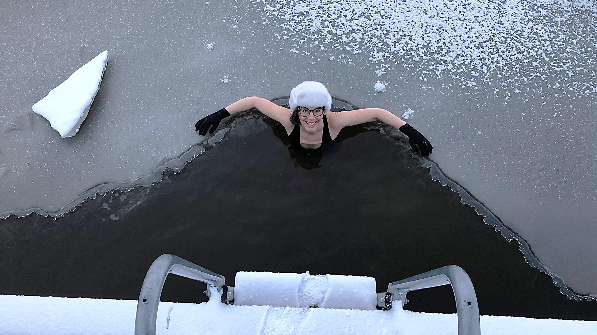 Kvinna med pälsmössa badar isvak. Foto: Pressbild