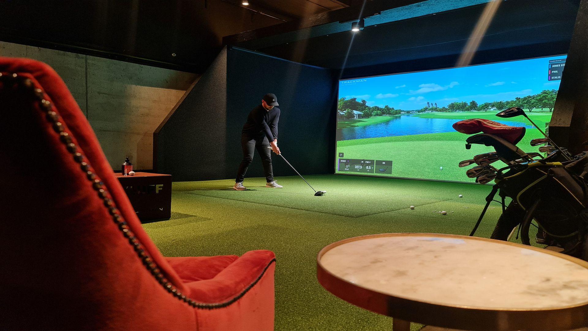 En man spelar golfsimulator på steam hotel. Foto: Pressbild