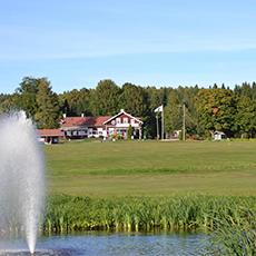 Vy över Fagersta golfklubbs klubbhus med fontän i förgrunden. Foto: Pressbild