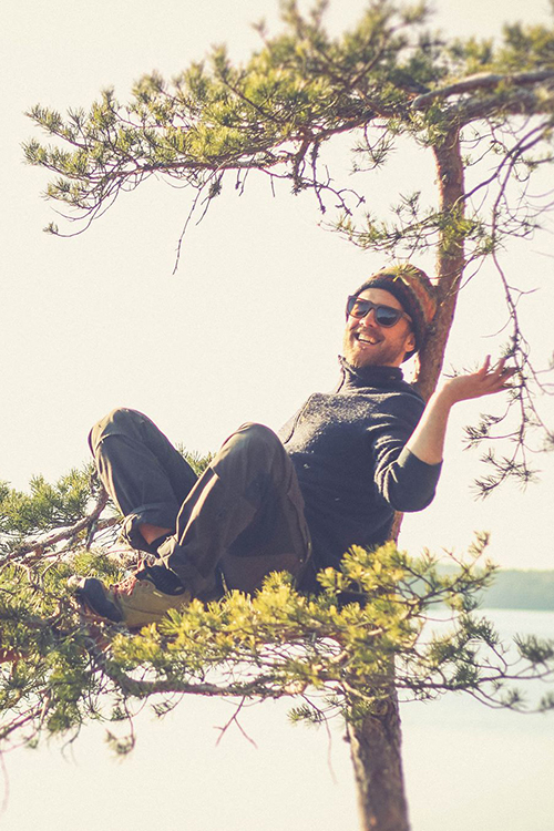 Marcus Eld sitter uppe i en liten tall och är glad. pressbild.