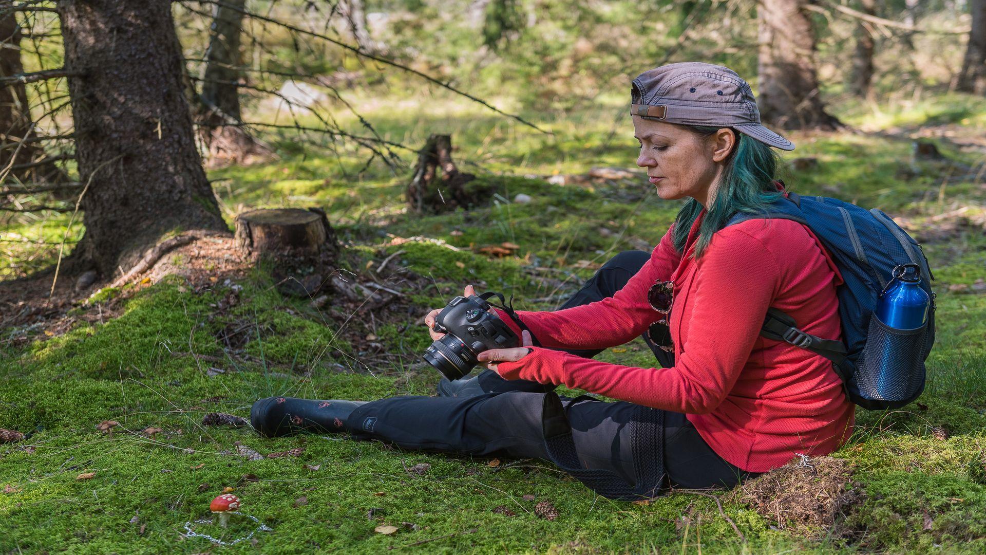 En kvinna sitter i skogen med kamerautrustning. Fotograf: Pressbild