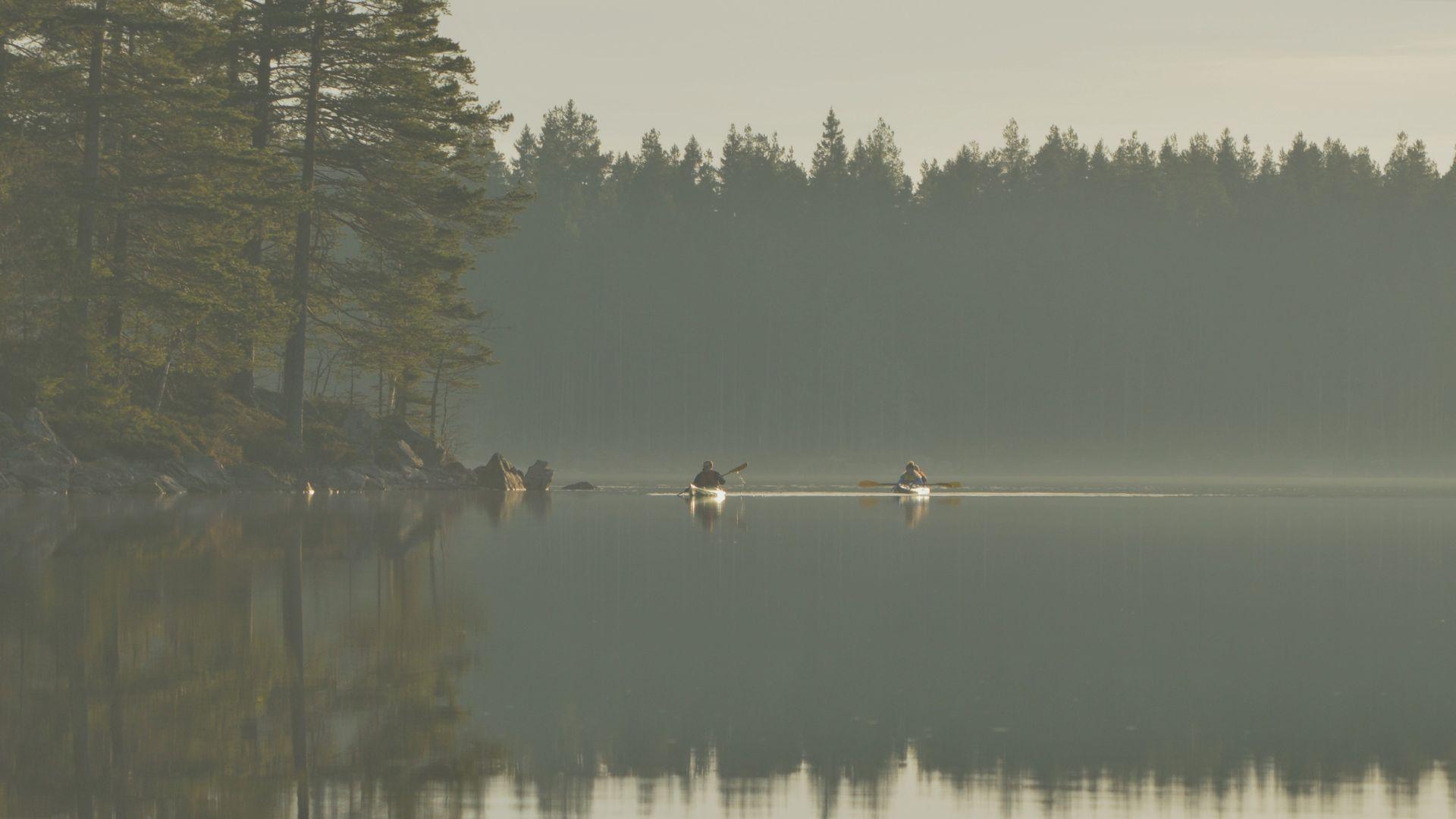 Två personer paddlar i varsin kajak på en dimmig sjö. Pressbild.