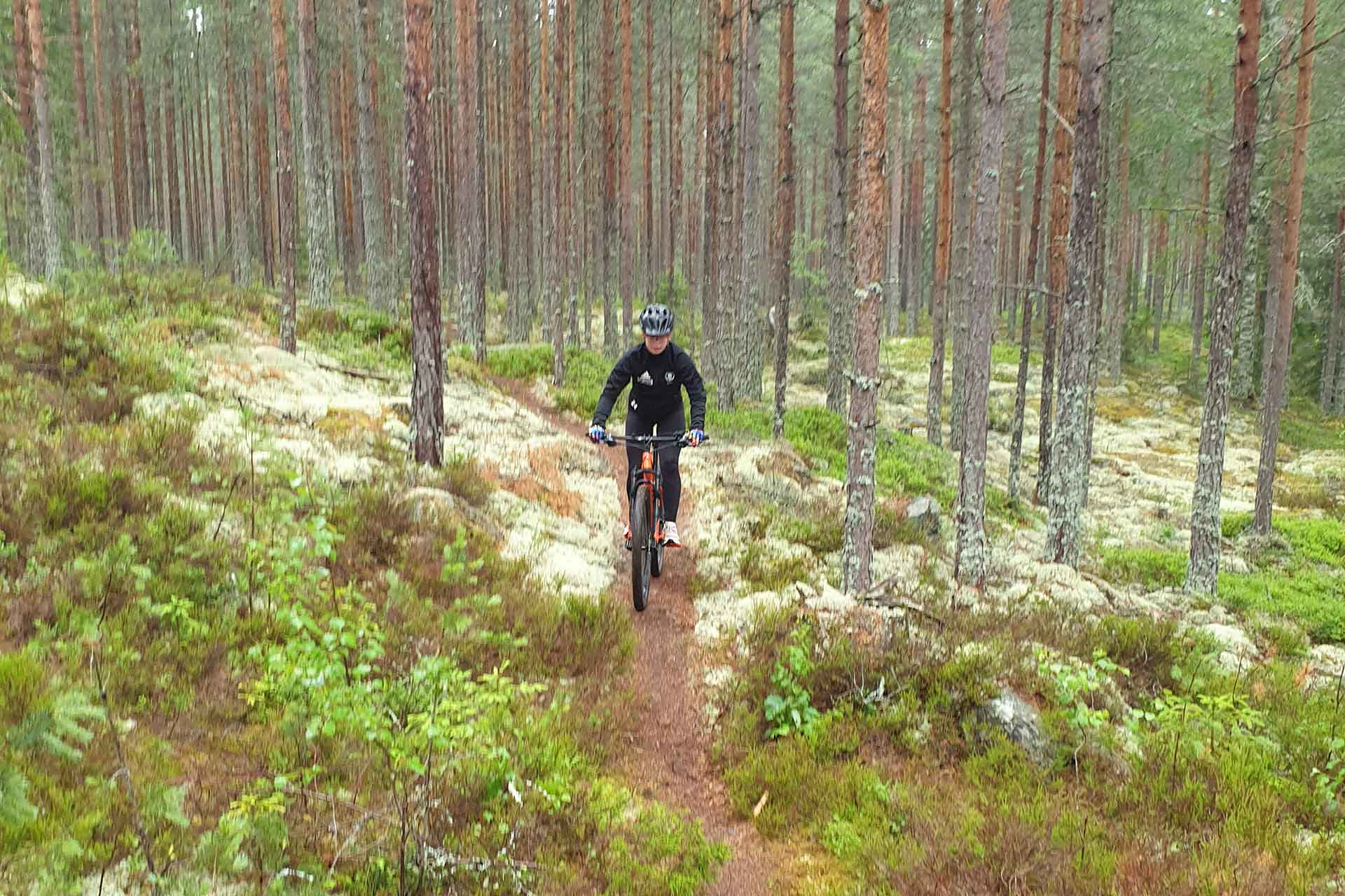 En flicka cyklar i skogen. Fotograf: Pernilla Wester