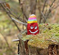 Färgglad stenfigur på en stubbe i skogen. Foto: Linda Heplinger