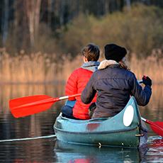 Två människor som paddlar iväg i en kanot. Pressbild