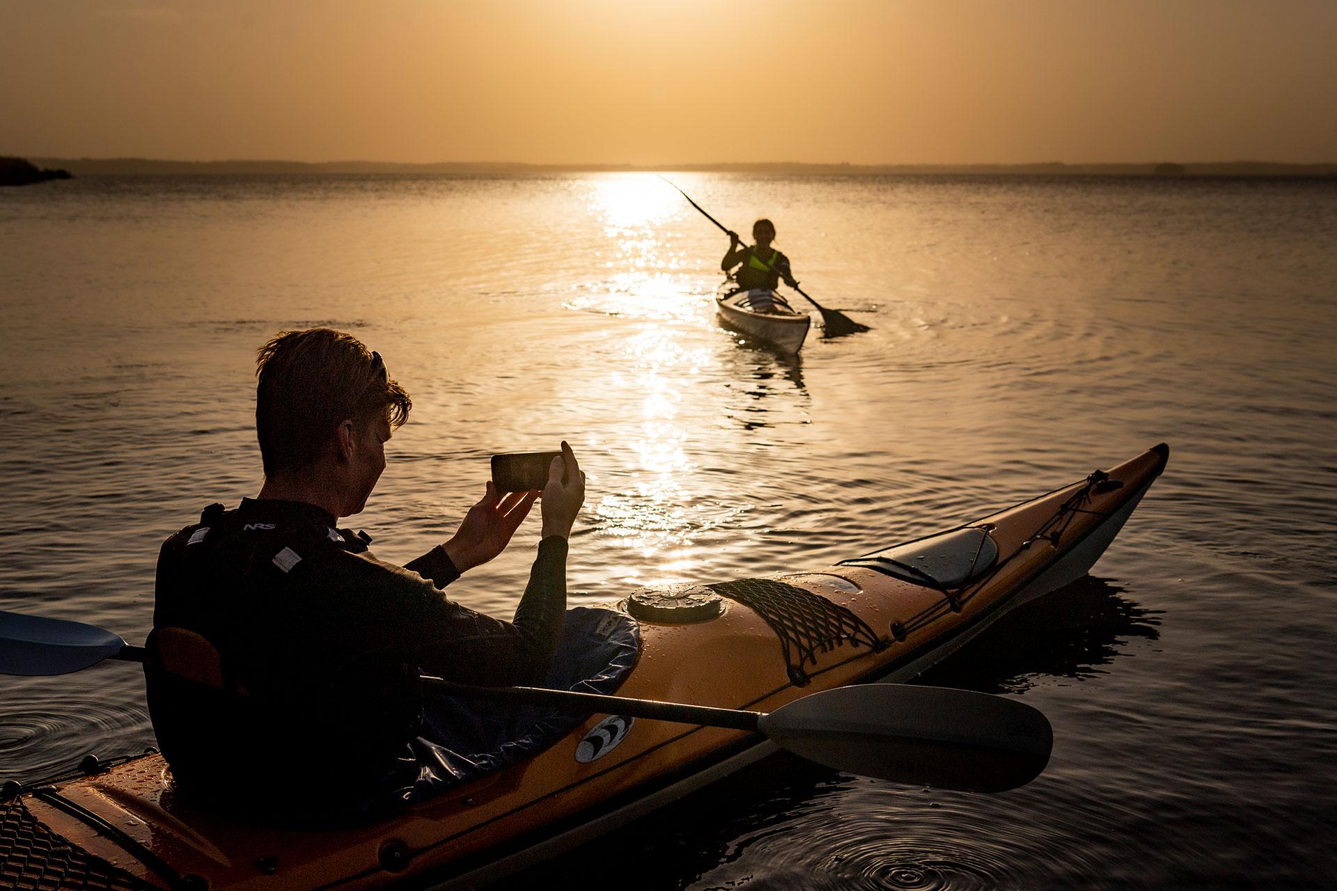 Två killar paddlar och fotograferar i solnedgången. Pressbild