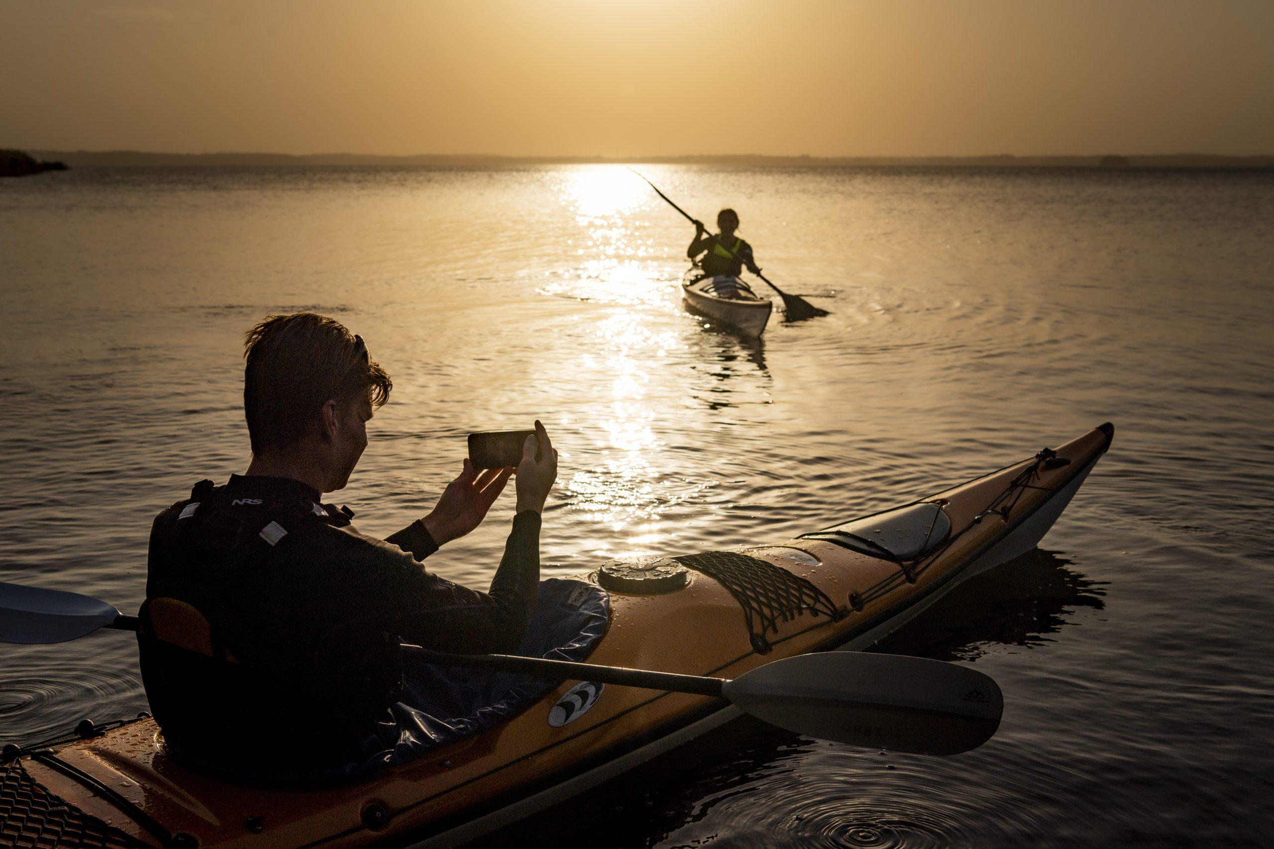 Två personer paddlar och fotograferar i solnedgången. Fotograf: Jonas Bilberg.