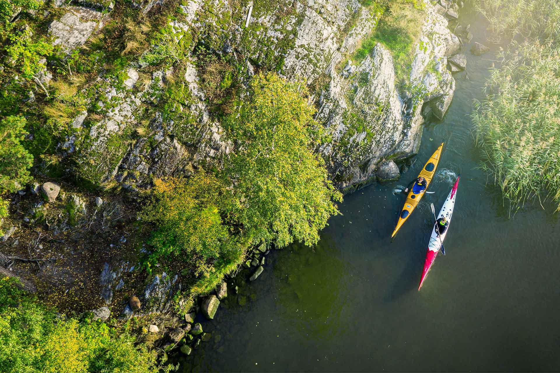 Vy ner från en klippa på två personer som paddlar kajak. Foto: Jonas Bilberg.
