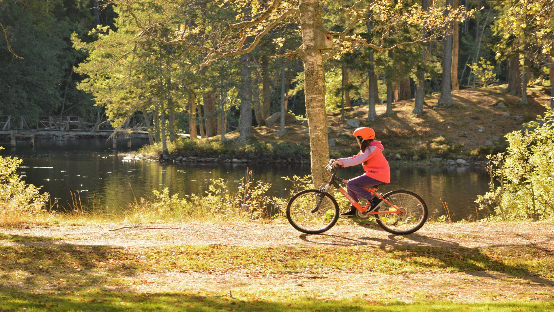 En flicka cyklar intill en sjö. Fotograf: Pressbild
