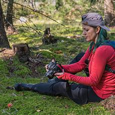Kvinna fotar i naturen, sittandes på marken. Pressbild