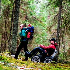 Familj vandrar i skogen, till fots och med terrängfordonet Zoom Uphill. Pressbild