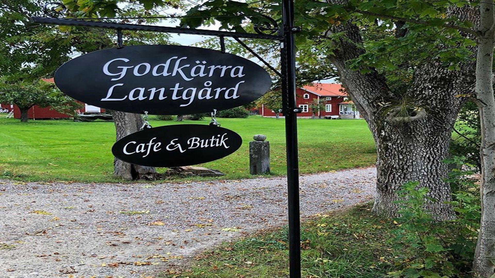 Vacker skylt och hus och grönska vid Godkärra lantgård. Fotograf: Pressbild