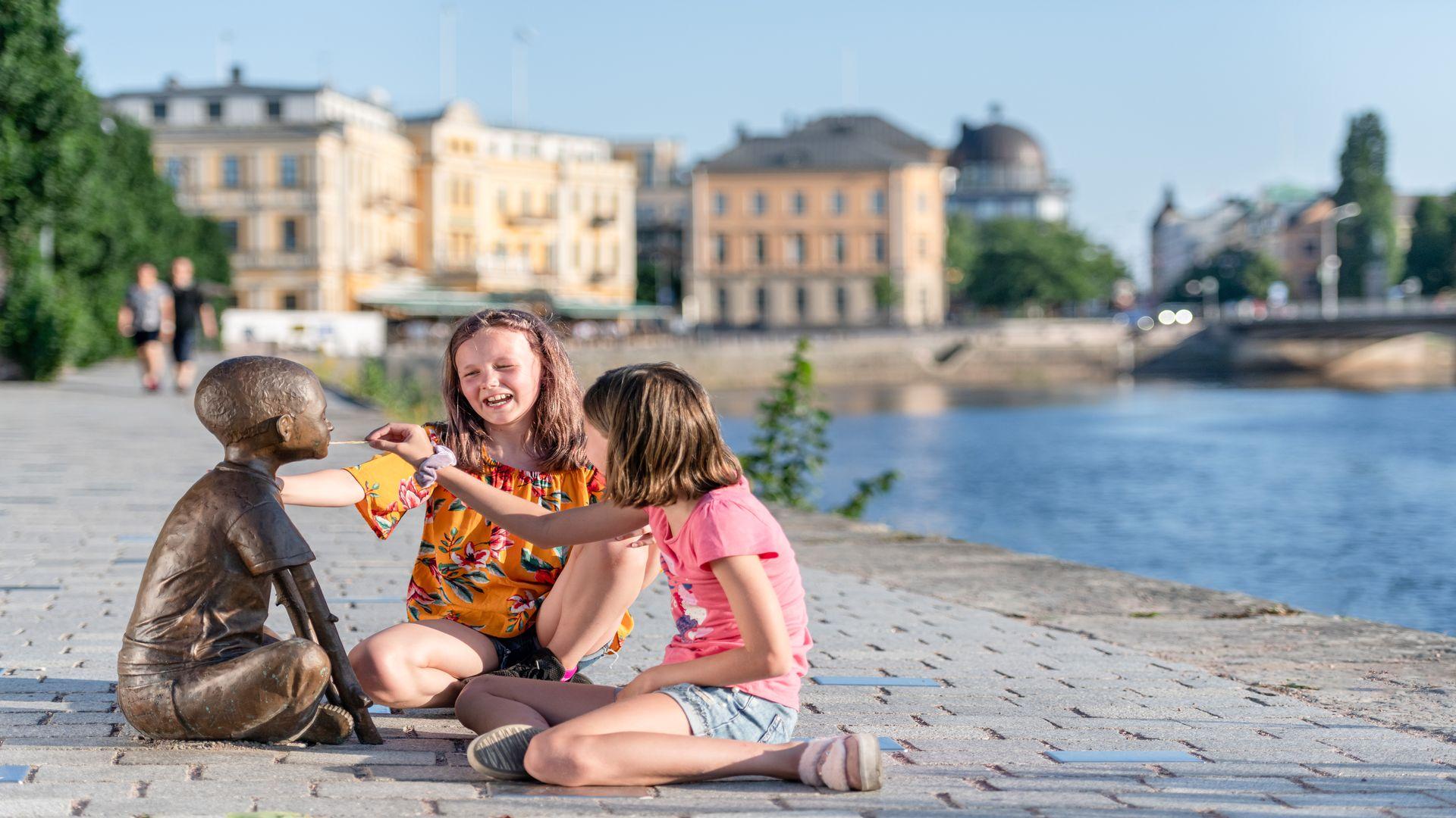 Två barn sitter intill vattenbrynet. Fotograf: Pressbild Karlstad