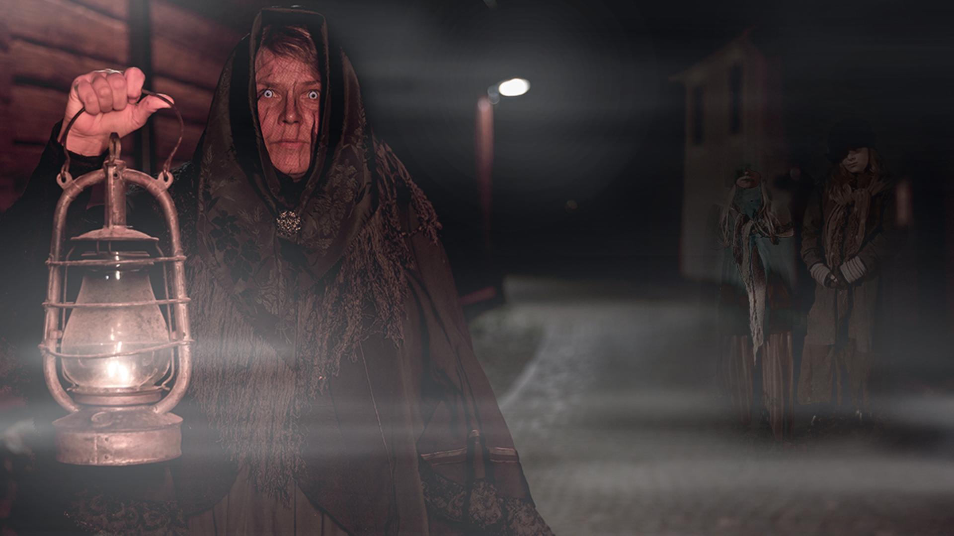Kvinna från förr stirrar in i kameran och håller en lykta i handen, i bakgrunden skymtar vålnader. Foto Therese Eriksson.